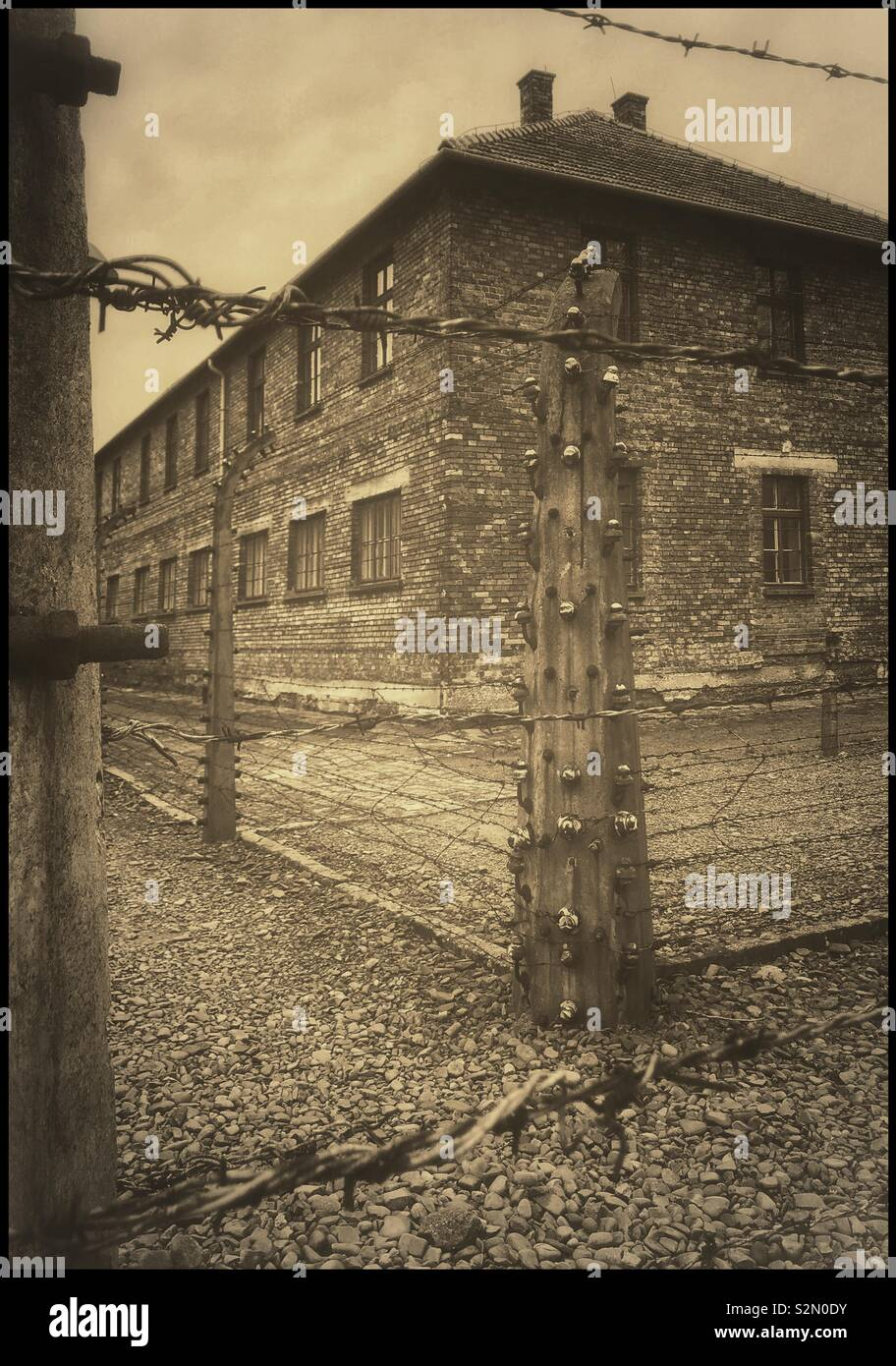One of the many buildings surrounded by an electric fence at the infamous Nazi Auschwitz Concentration Camp near Kraków in Poland. A site of mass genocide during the 1940's. Now a UNESCO W.H.S. - Stock Image