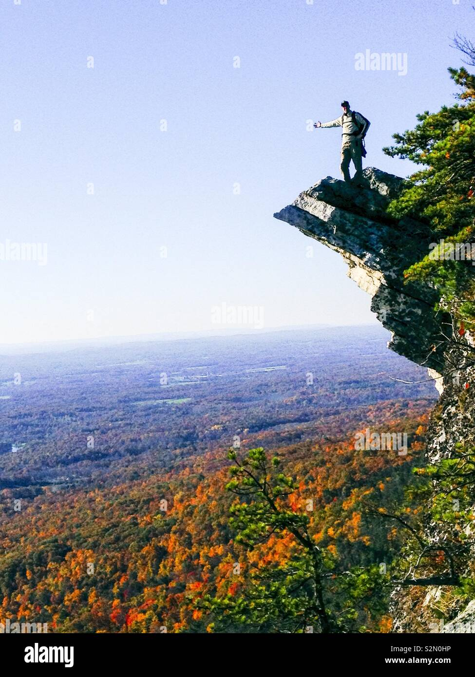 Hiker atop precipitous outcropping in New York State Shawanagunks in autumn Stock Photo