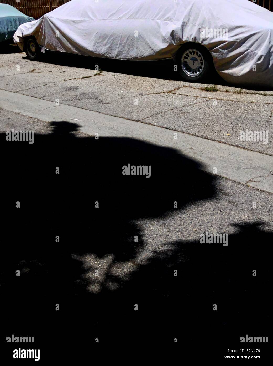 Tarp covers a large limo parked in an alley Stock Photo