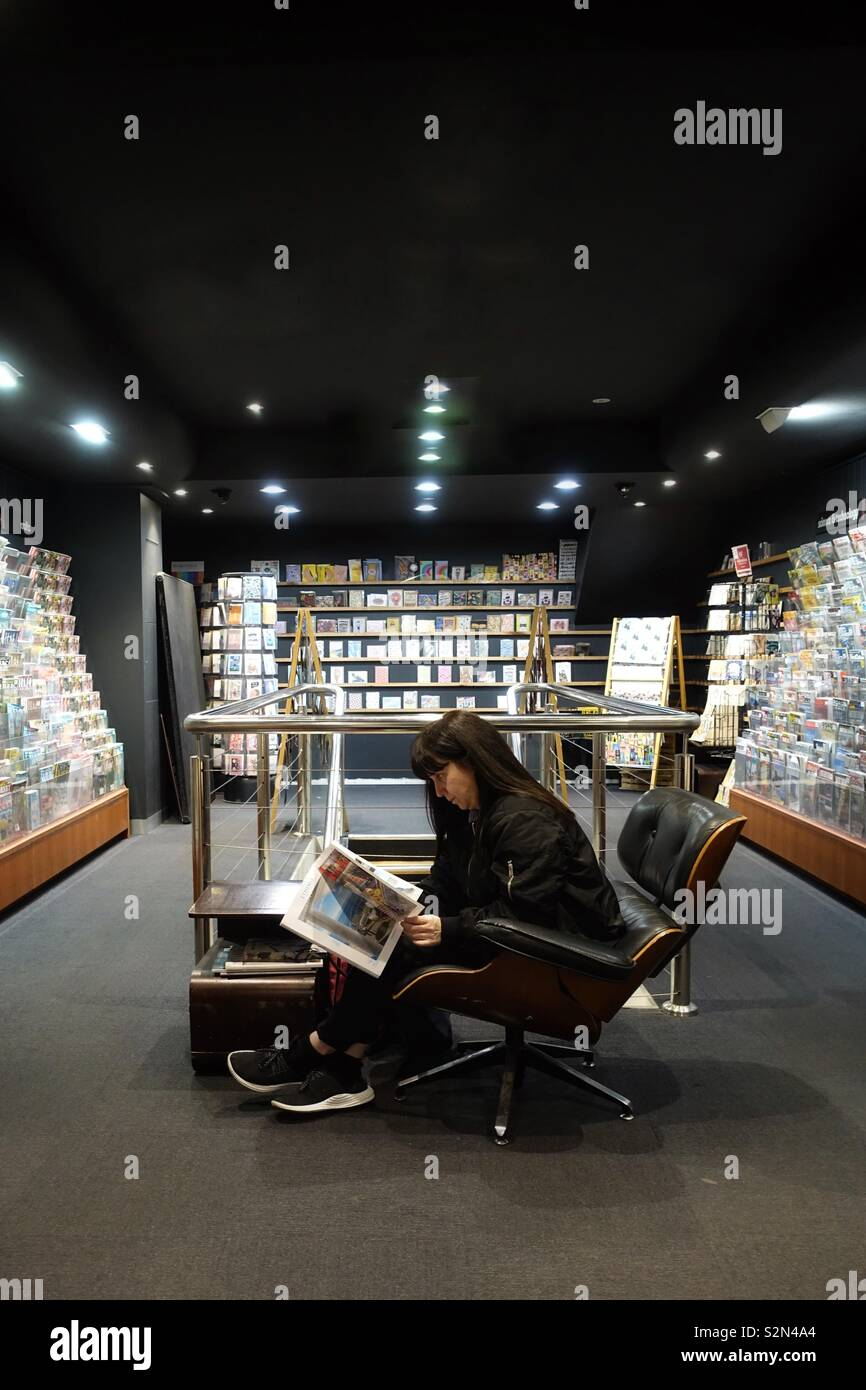 Woman in a magazin shop. Sitting in an designer chair and reading. - Stock Image
