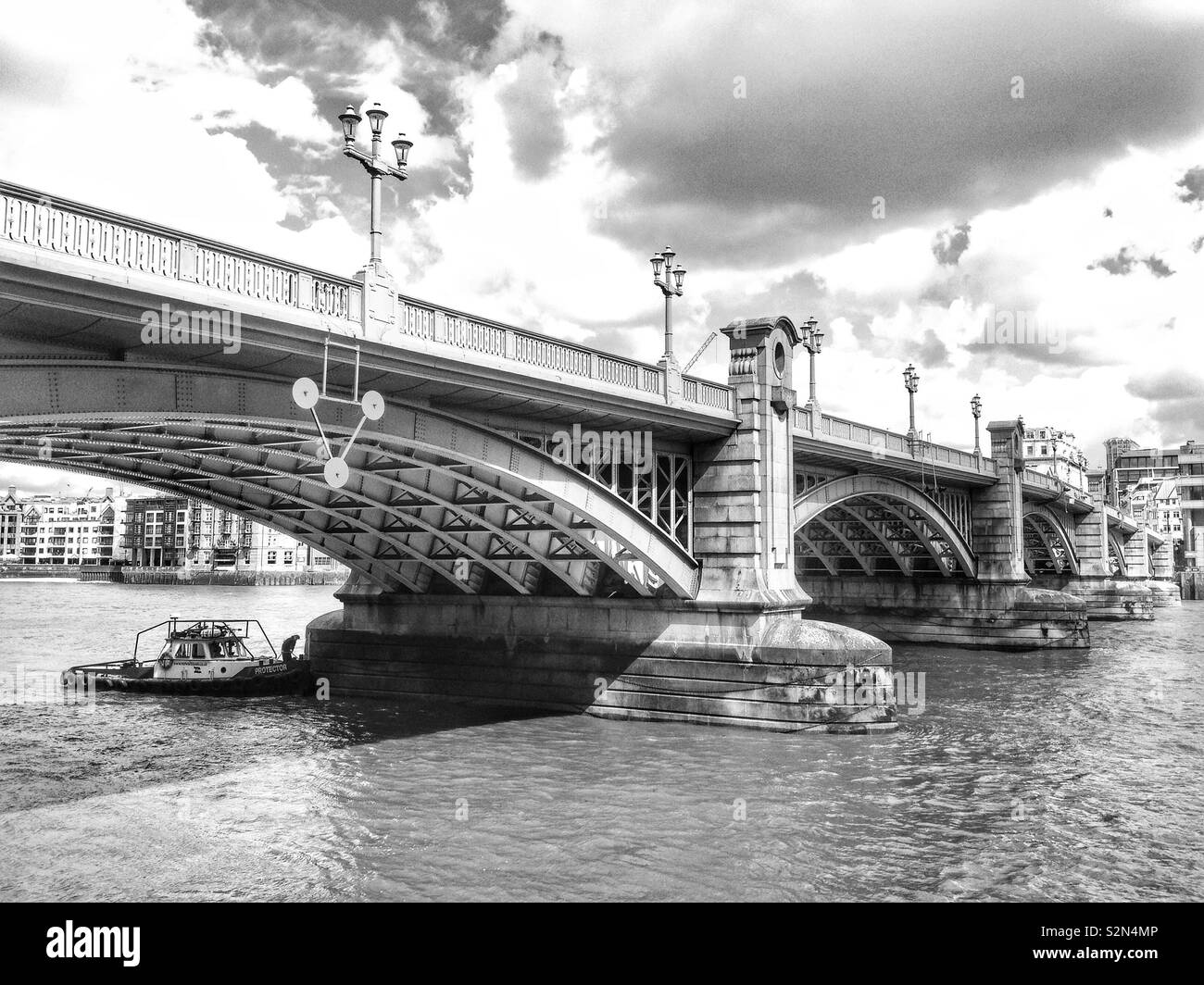 A boat moored under the arches of Southwark Bridge on the River Thames in London, England, looking towards the north bank. - Stock Image