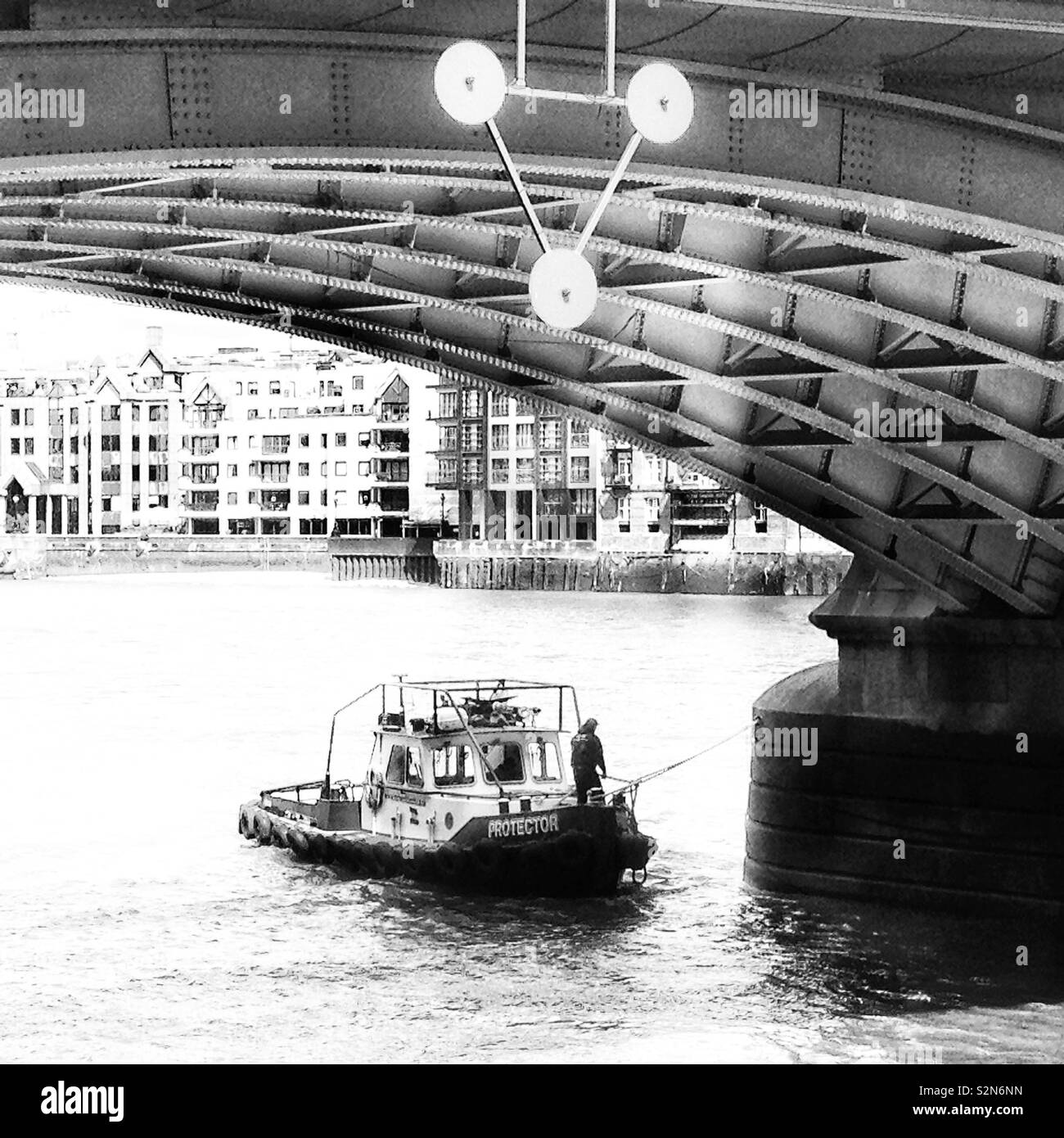 A tugboat moored under one of the arches of Southwark Bridge on the River Thames, London, England. - Stock Image