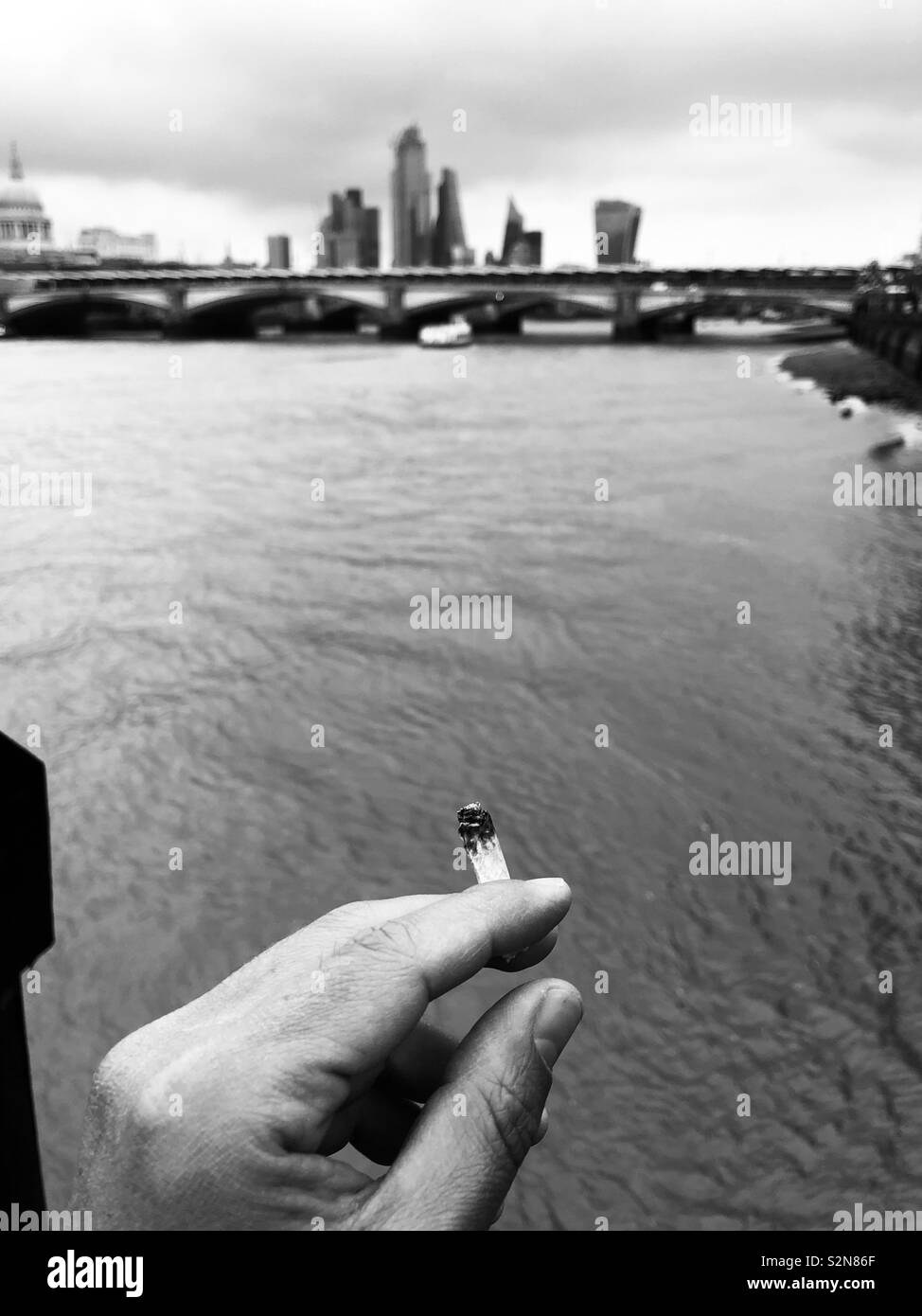 Hand of a man who is smoking by the river Thames - Stock Image