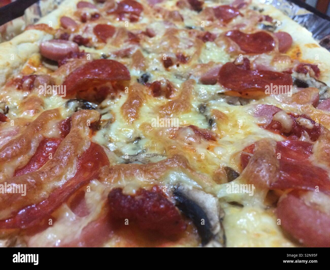 Pizza with pepperoni and mushrooms - Stock Image