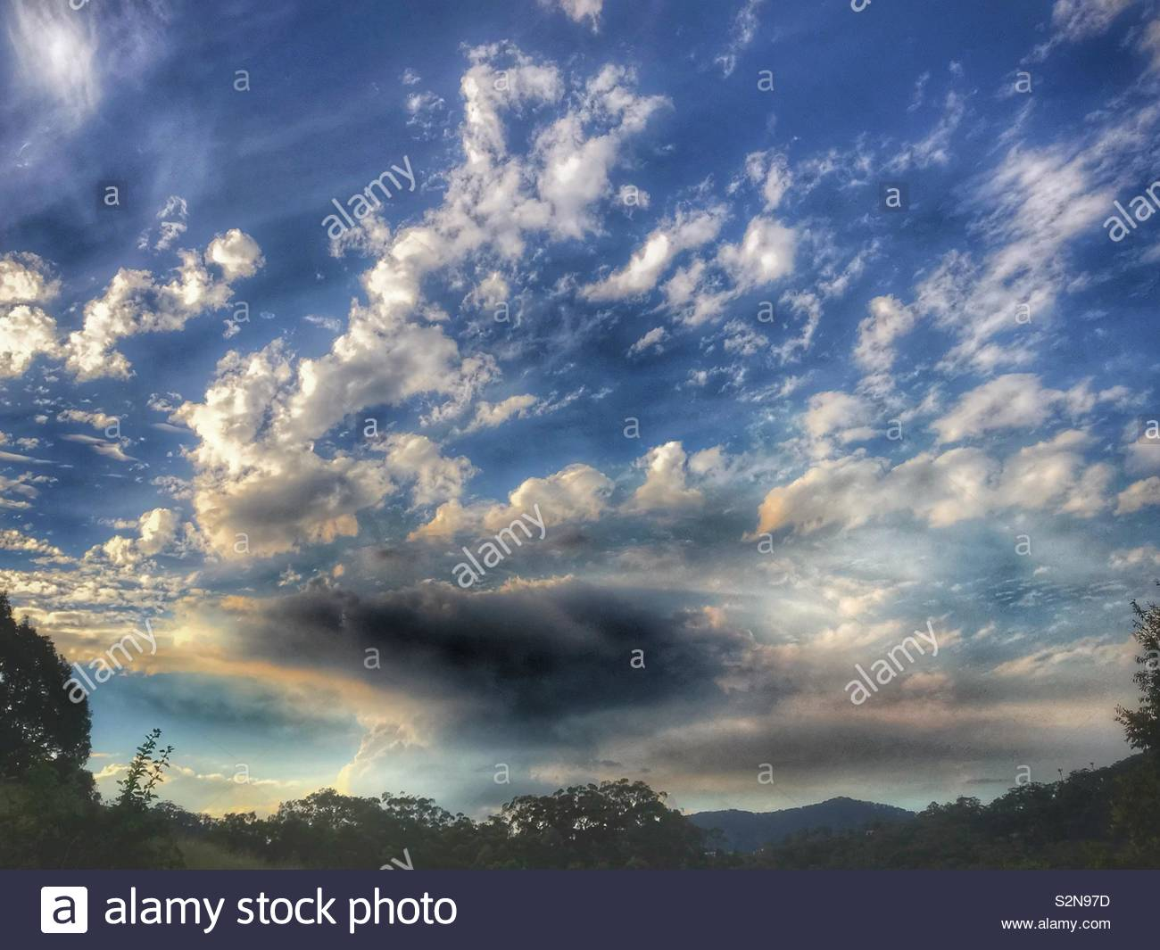 Sunlight shining through Autumn Afternoon cloud cover against blue sky in Australia - Stock Image