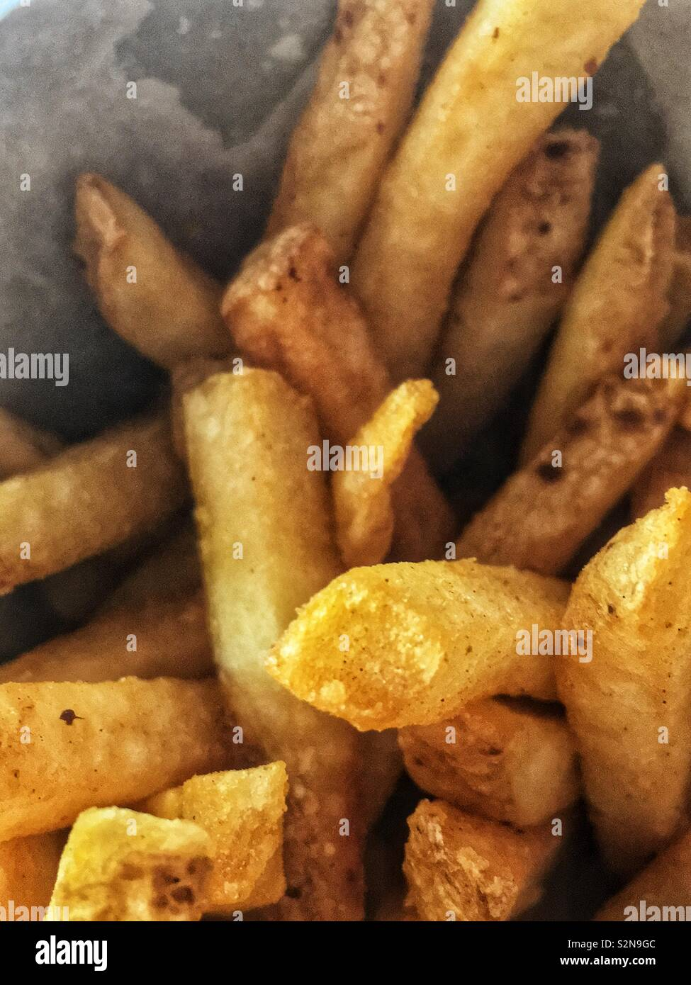 Closeup of fresh delicious tasty French fries served in wax paper. - Stock Image