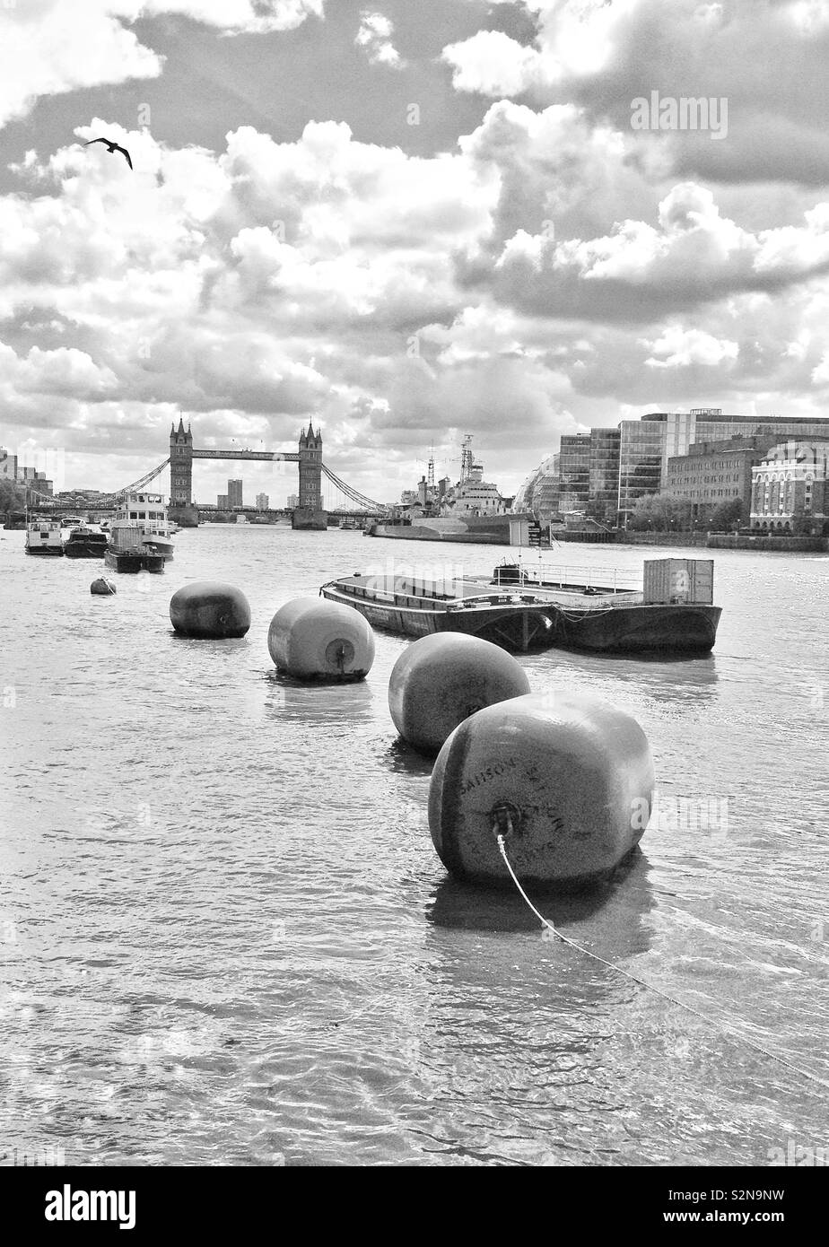A view along the River Thames in London, England, looking towards Tower Bridge and City Hall. - Stock Image