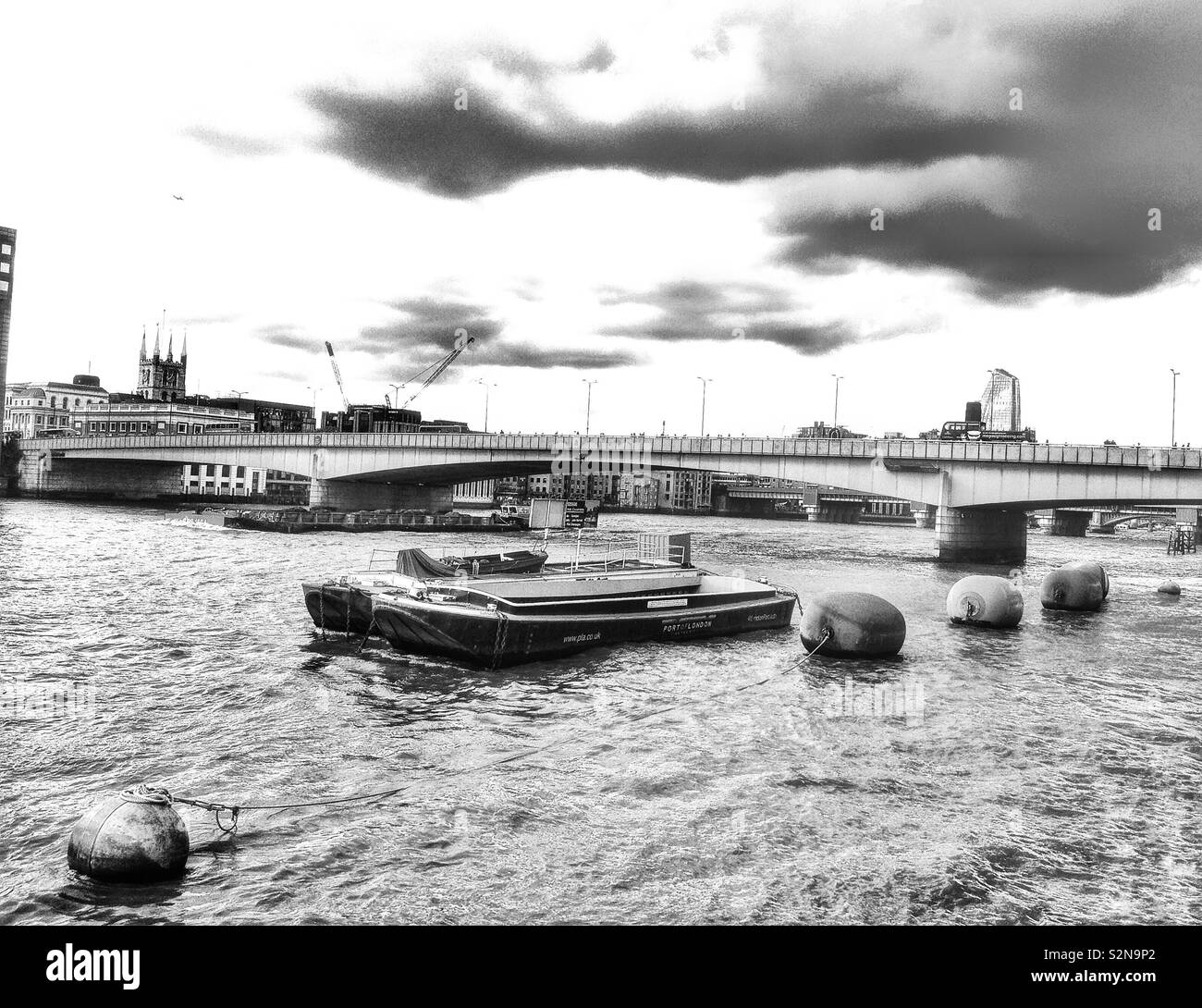 The River Thames in London, England, on an overcast day, looking towards London Bridge. - Stock Image