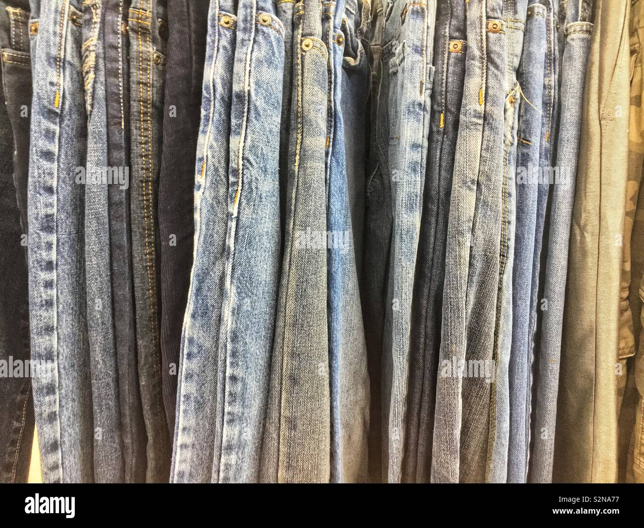 61f19c0b5e A variety of fashionable jeans and pants hanging on a rod Stock ...