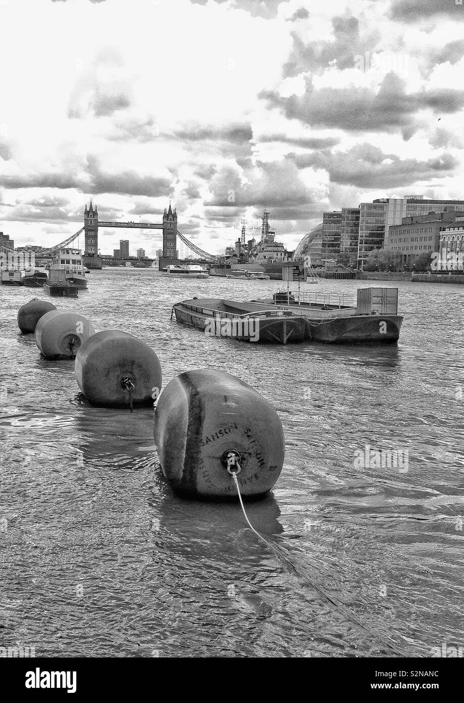 View along an overcast River Thames in London, England, looking towards the iconic Tower Bridge. Stock Photo