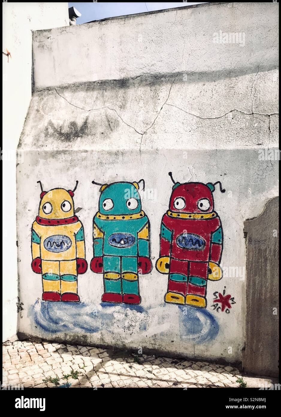 Graffiti or Art? Three extra-terrestrials painted onto a grimy white wall are standing in front of you. What are they looking at? What are they thinking? Photo Credit - © COLIN HOSKINS. - Stock Image