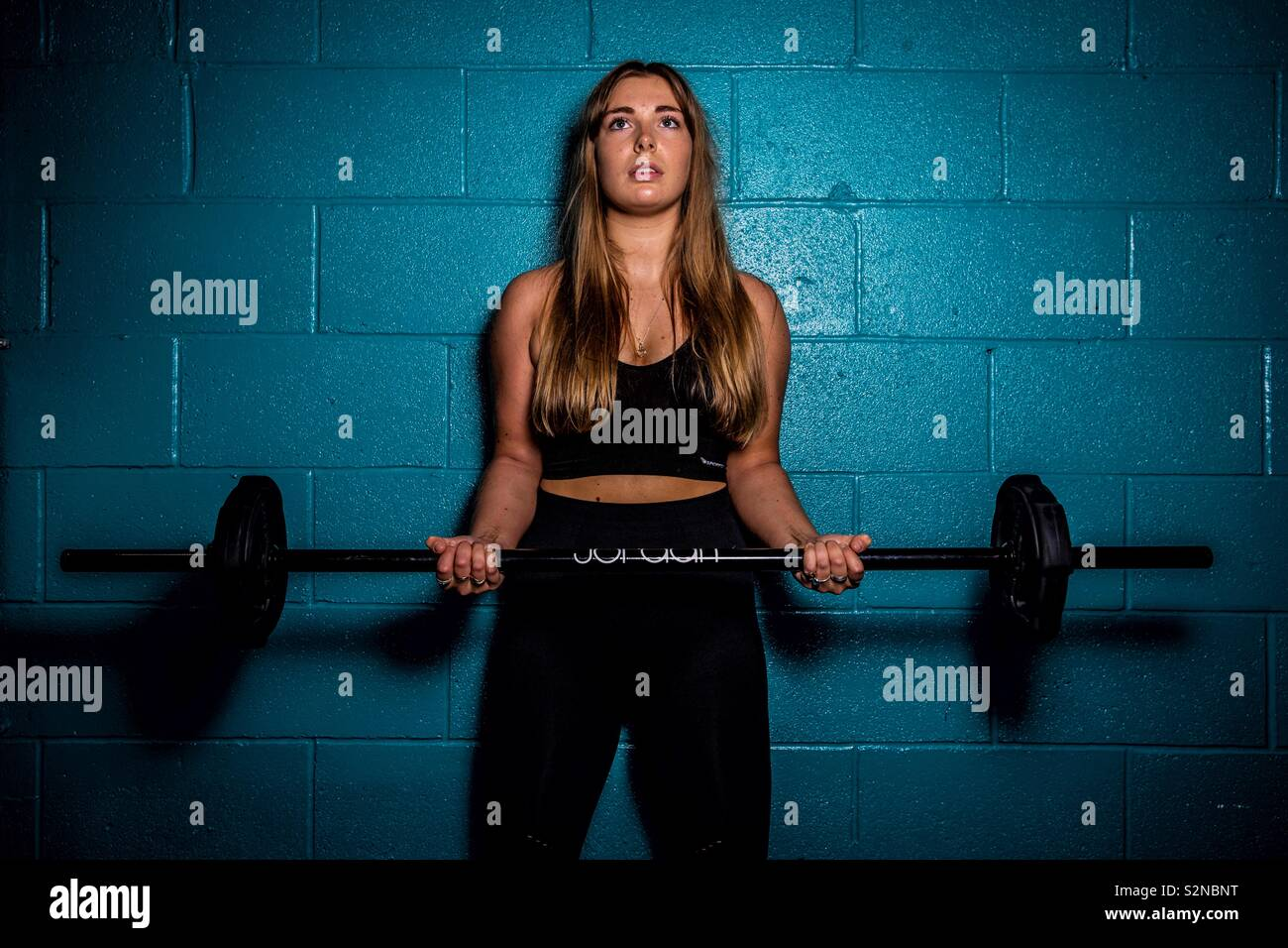 Woman lifting barbell at the gym. - Stock Image
