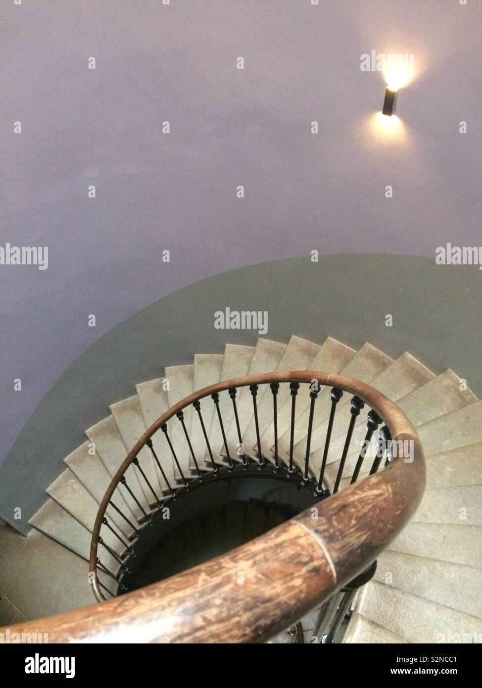 The staircase of an old French château with walls painted in two tones of grey - Stock Image