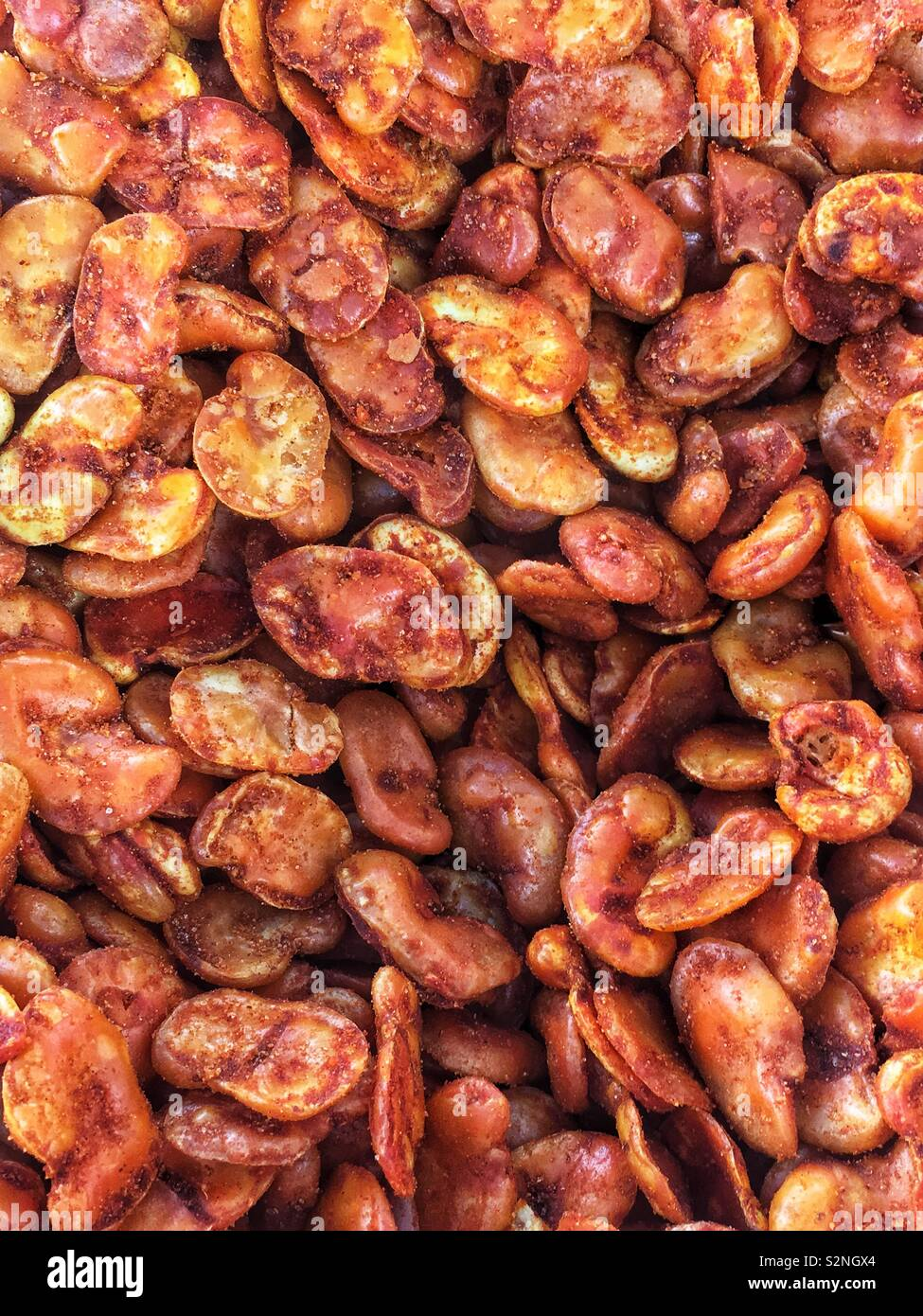 Full frame of dried fava beans dusted in red chili powder as a delicious natural and popular snack. - Stock Image