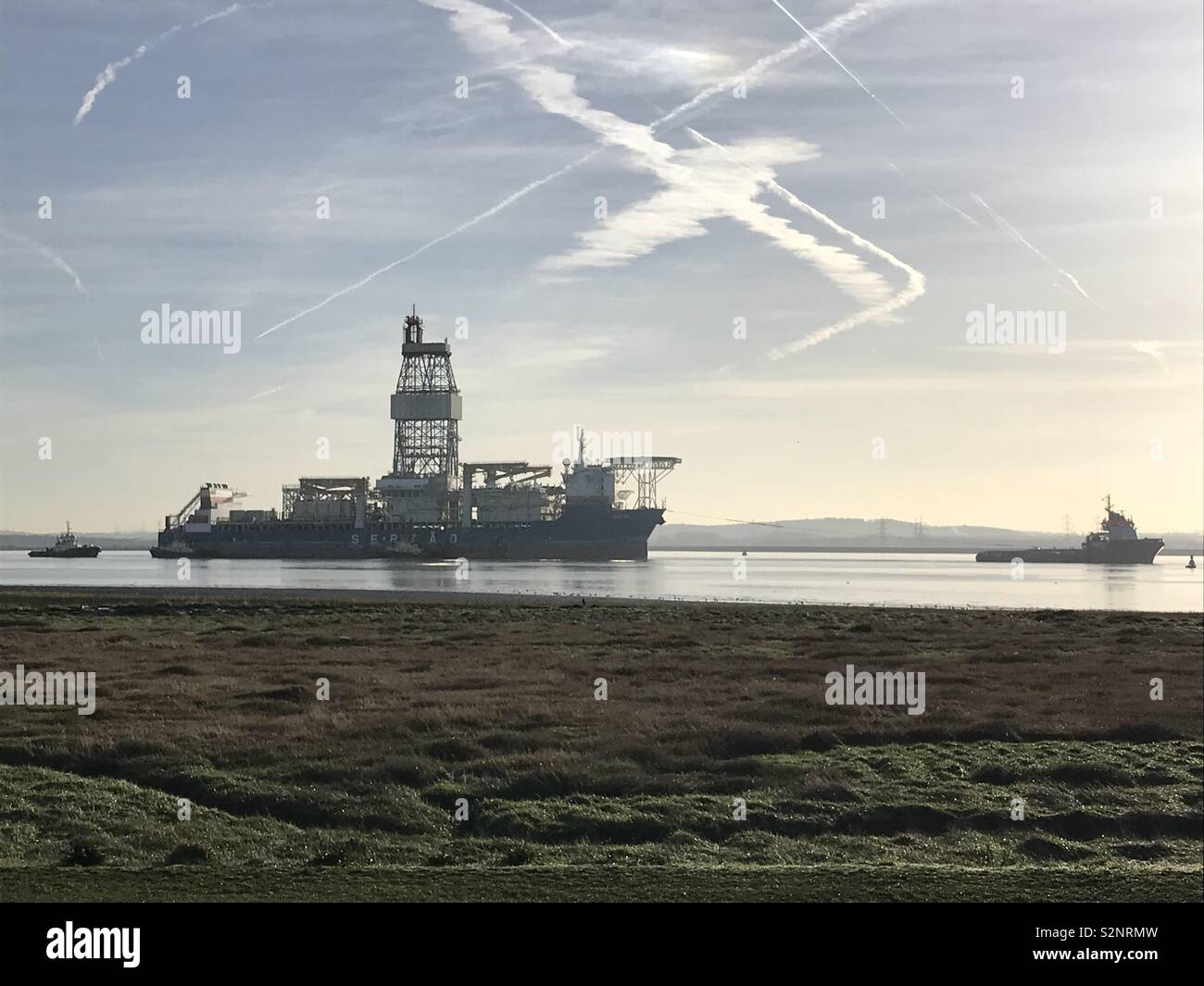 Drill ship Sertao being towed to Tilbury power station for layup, here seen passing East Tilbury - Stock Image