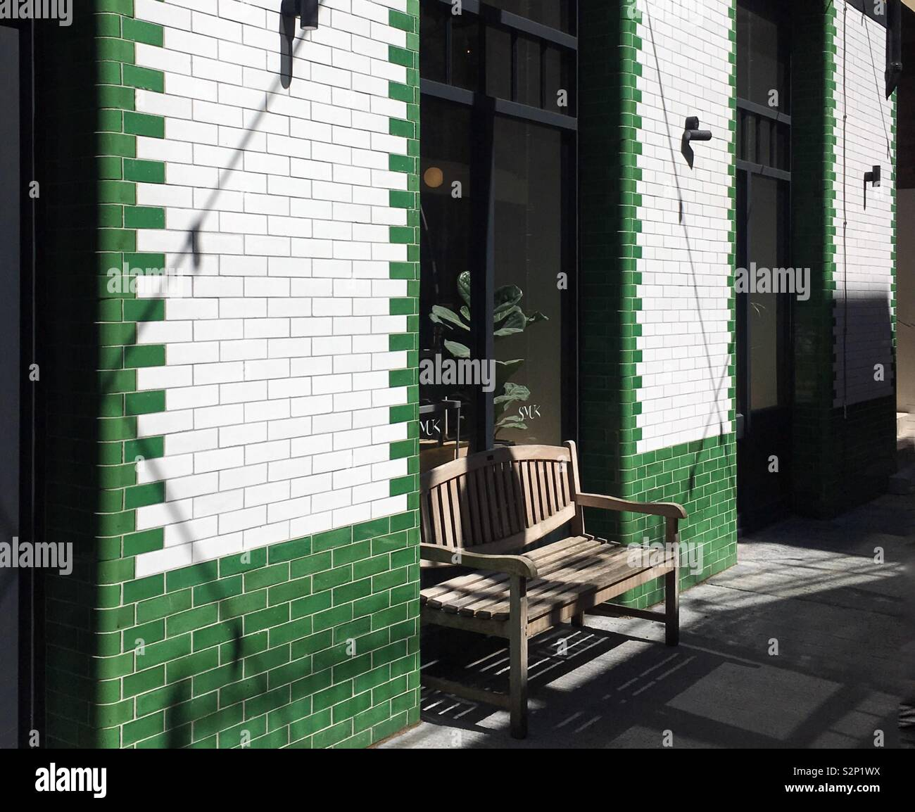 Strange A Wooden Bench Standing Against A Wall Clad In Green And Alphanode Cool Chair Designs And Ideas Alphanodeonline