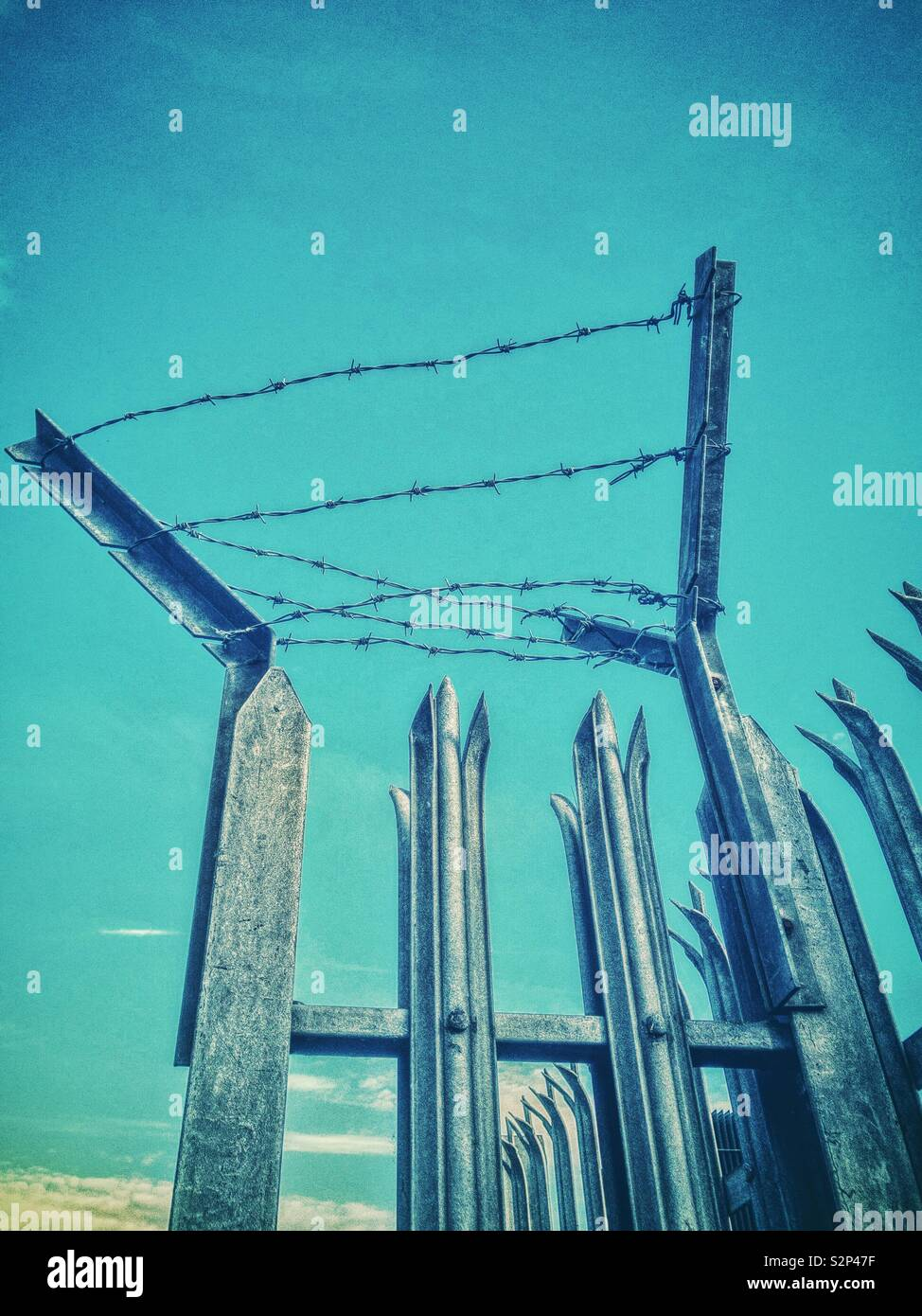 Metal security fence with barbed wire and spiked tops. - Stock Image