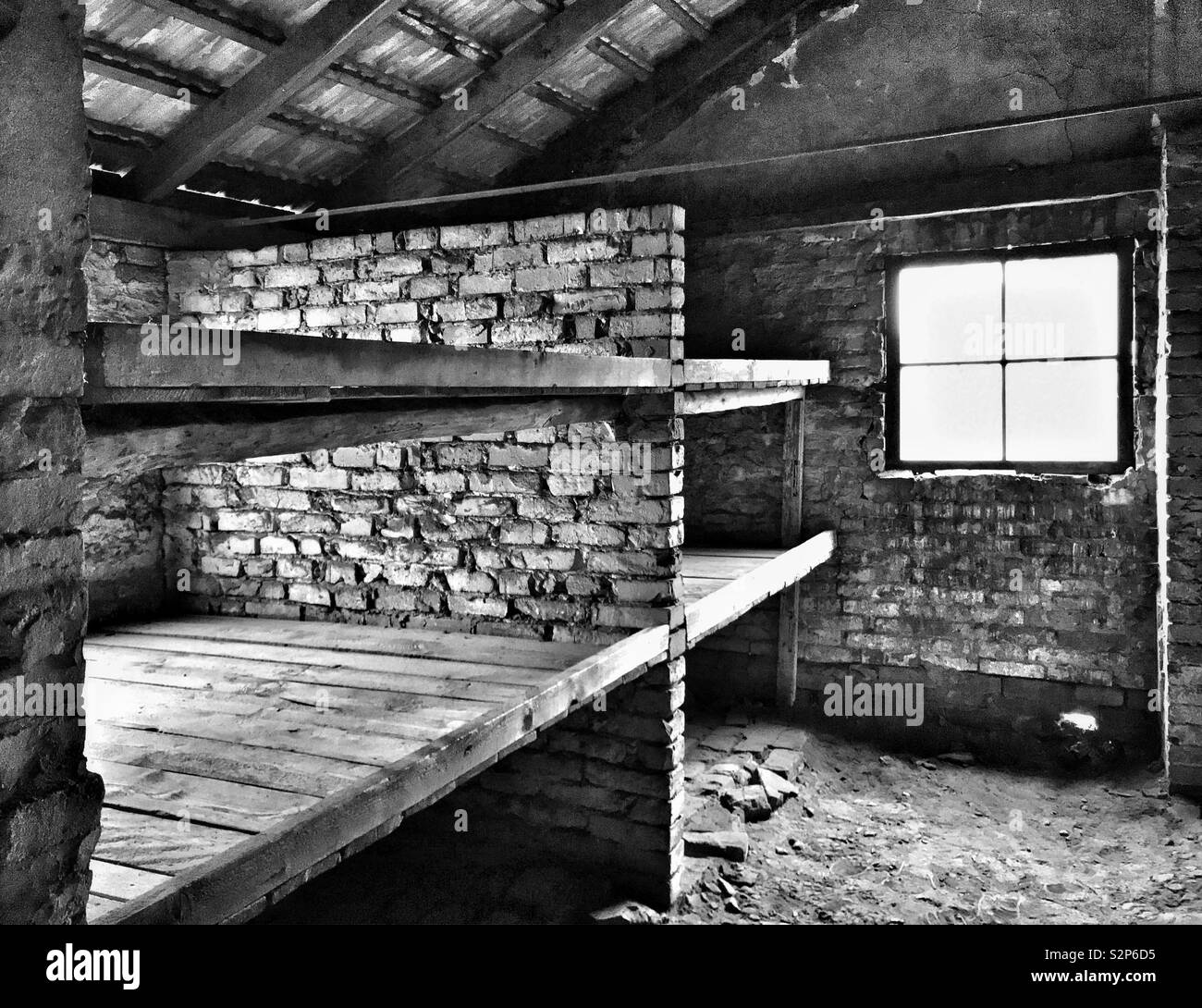 The interior of one of the surviving huts at the Nazi Auschwitz II - Birkenau Concentration Camp-in Poland. This was the sleeping quarters where many people crammed together and some starved to death. - Stock Image
