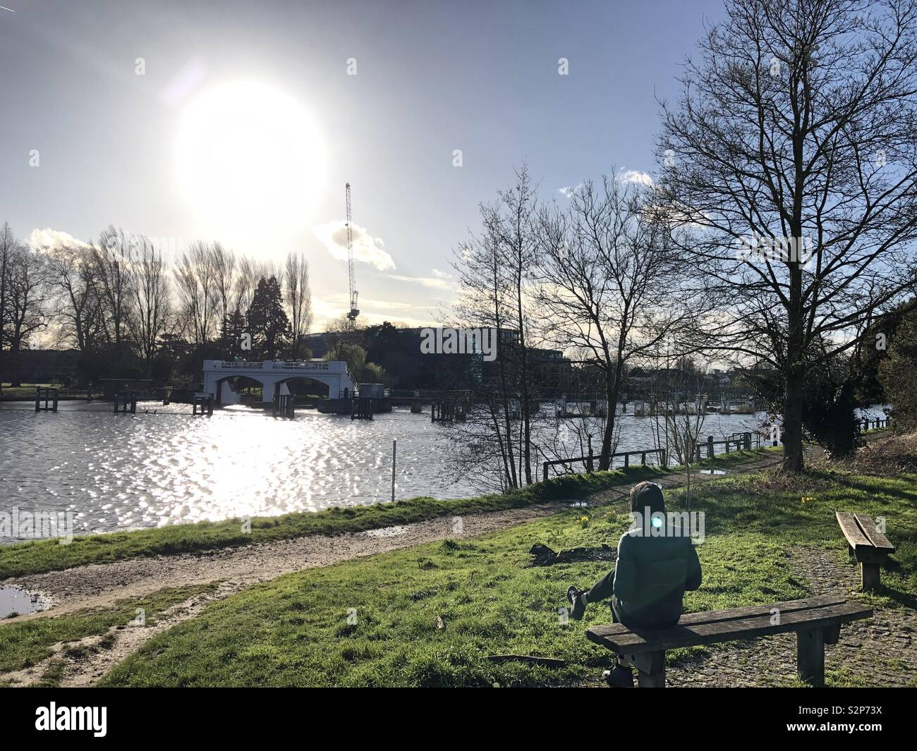 Photo was taken on a beautiful spring day on a walk along the River Thames Towpath on Kingston side looking across to Teddington Lock. - Stock Image