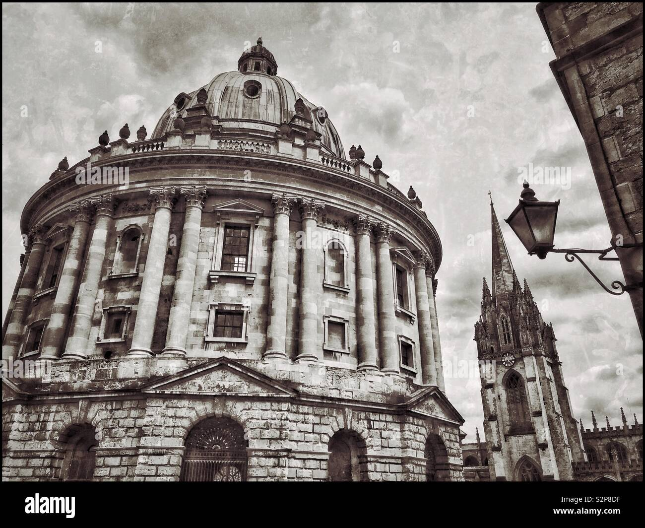 The Radcliffe Camera Building in Oxford, England. Not a real camera - but a library used by the students of Oxford University. The tall spired church is the University Church Of St. Mary the Virgin. © - Stock Image