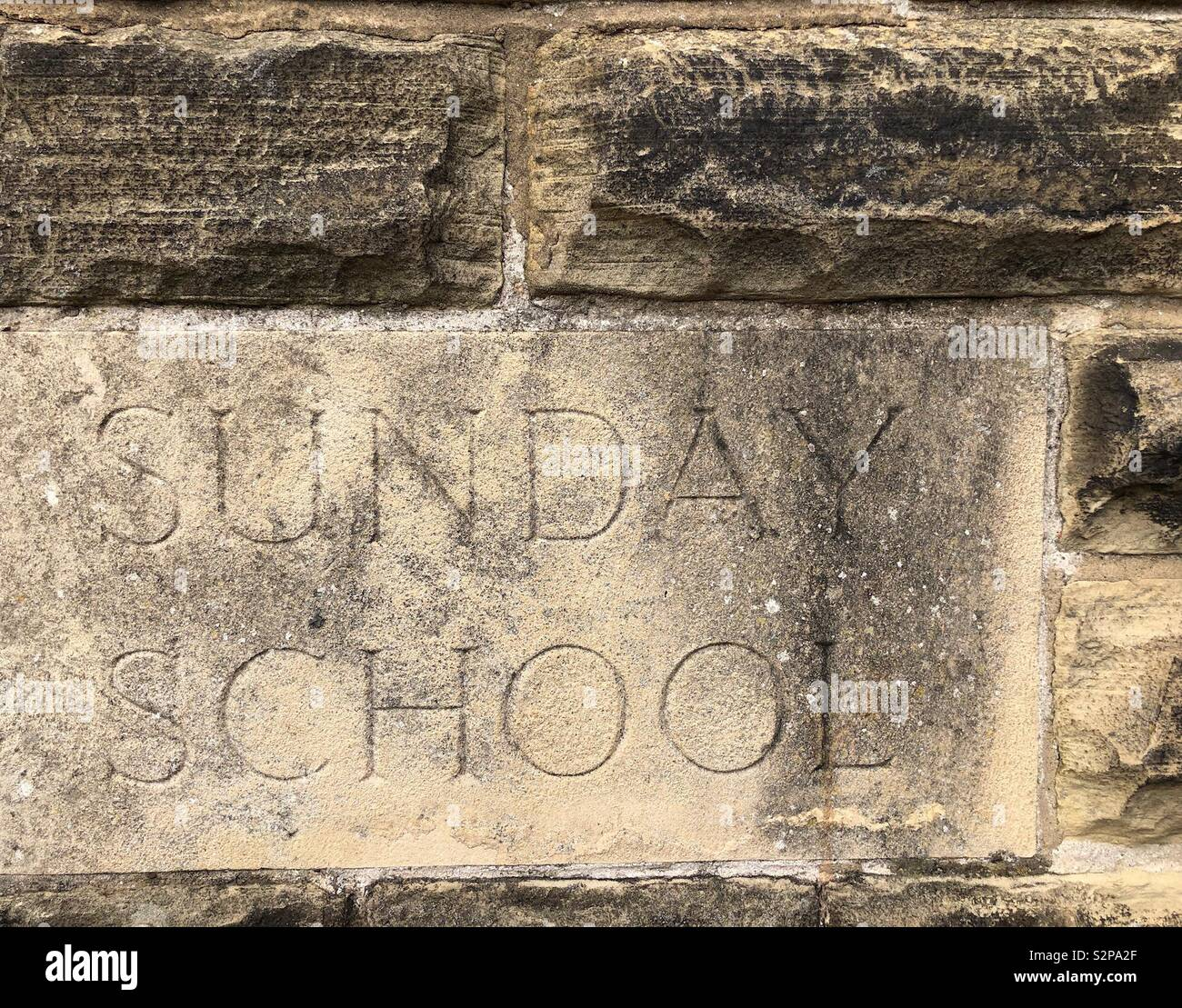 Carved stone embedded in the wall of a Methodist church  - Sunday School - Stock Image
