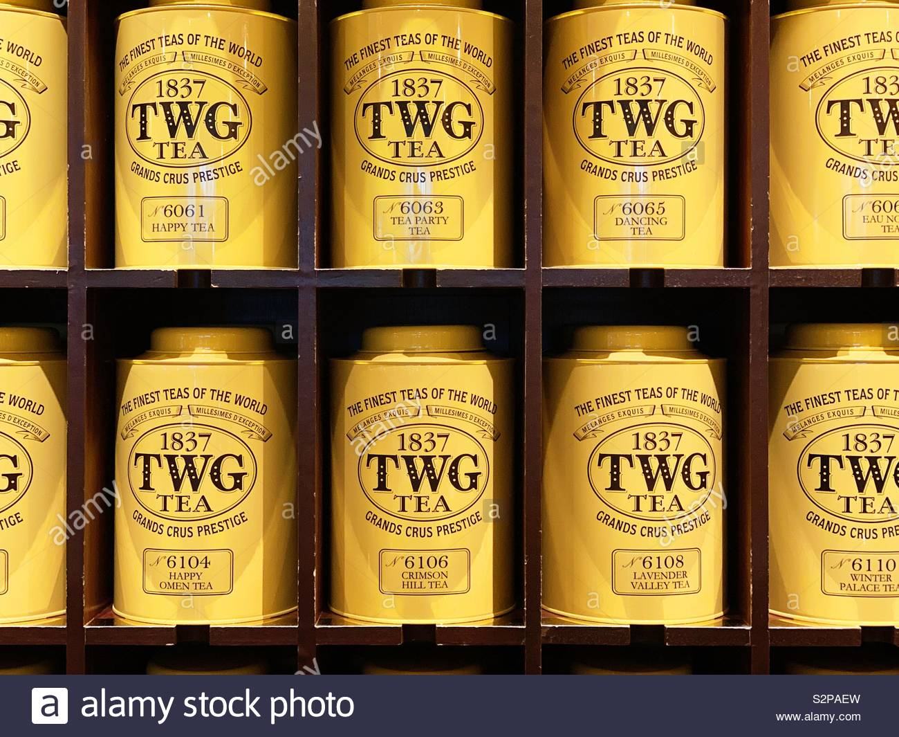 TWG yellow tea tins on the shelf in their shop in Singapore. - Stock Image