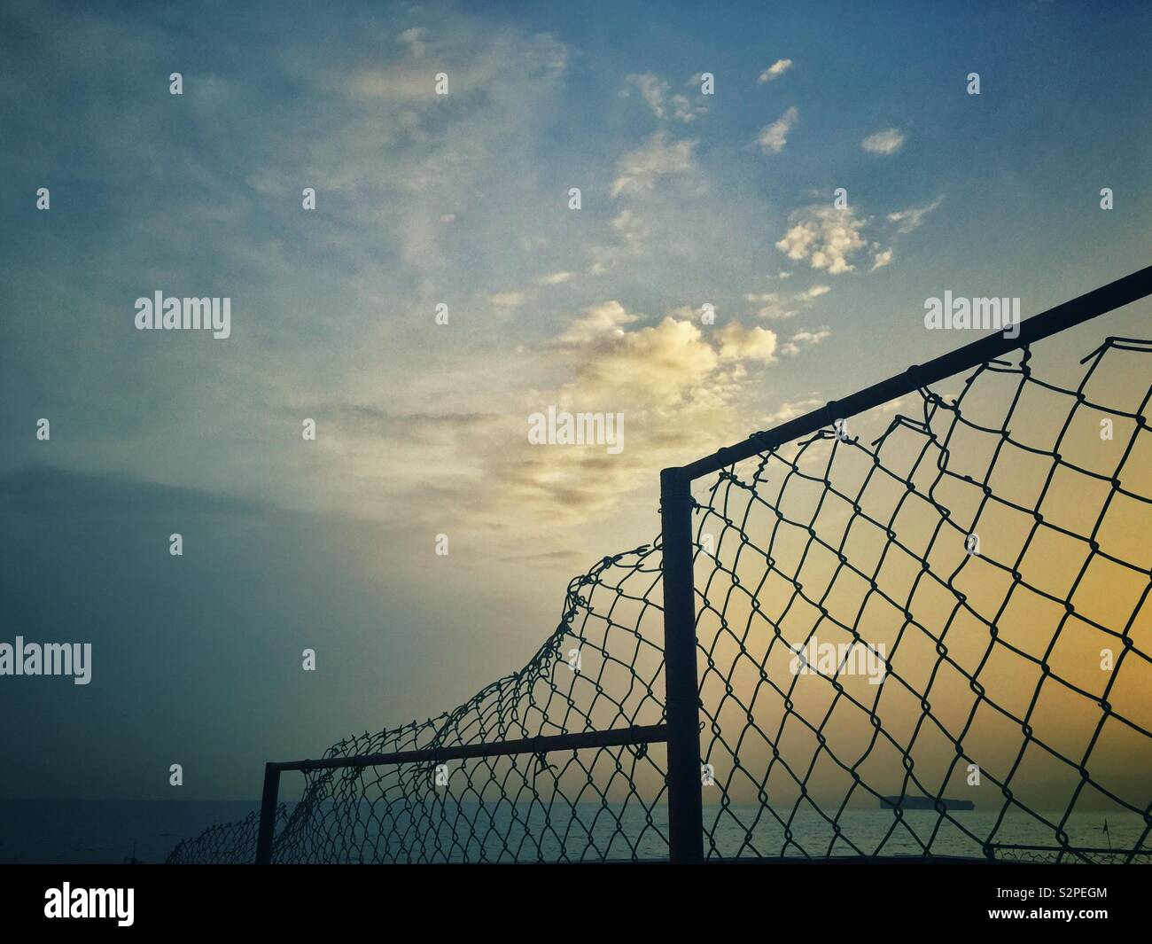 Broken chicken wire fence on the beach at sunrise Stock Photo