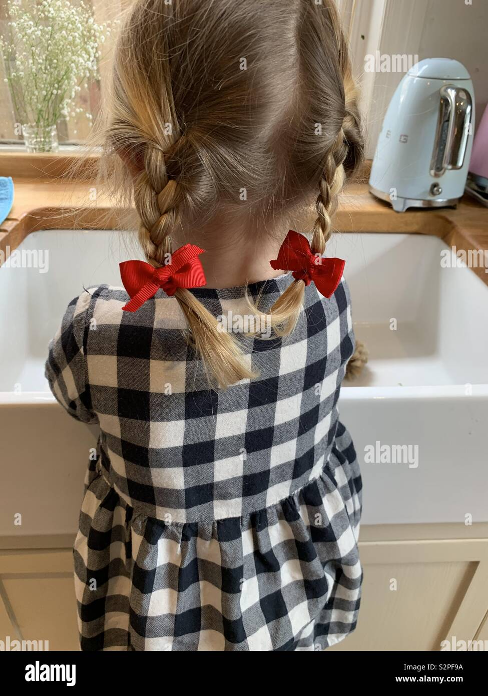 Little girls plaits with red bows - Stock Image