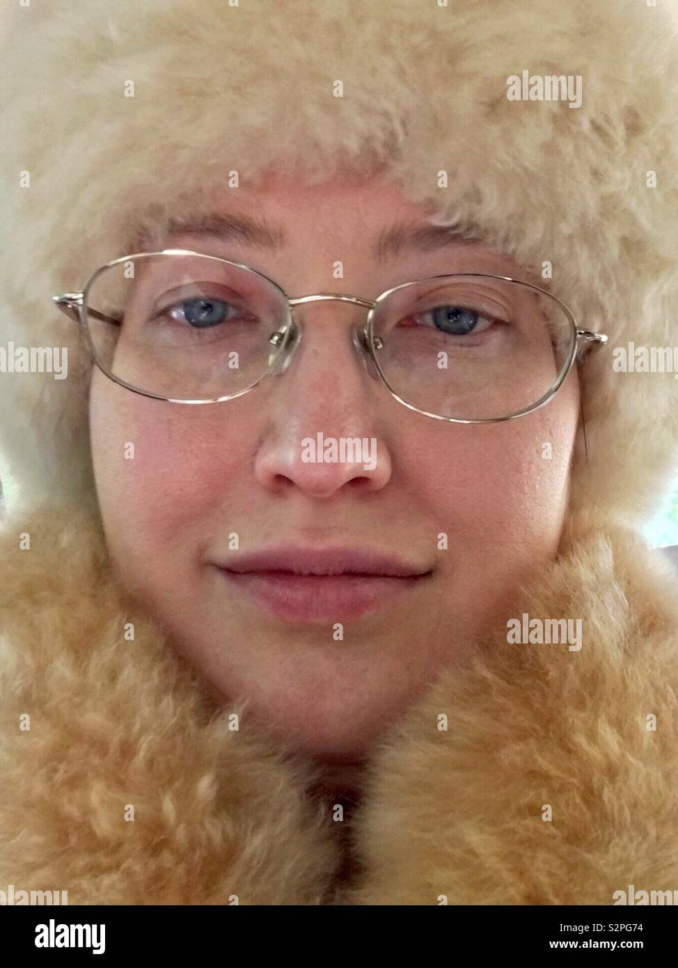 Face of Caucasian woman with blue eyes and gold rimmed glasses wearing cruelty free no-kill alpaca fur hat and scarf Stock Photo