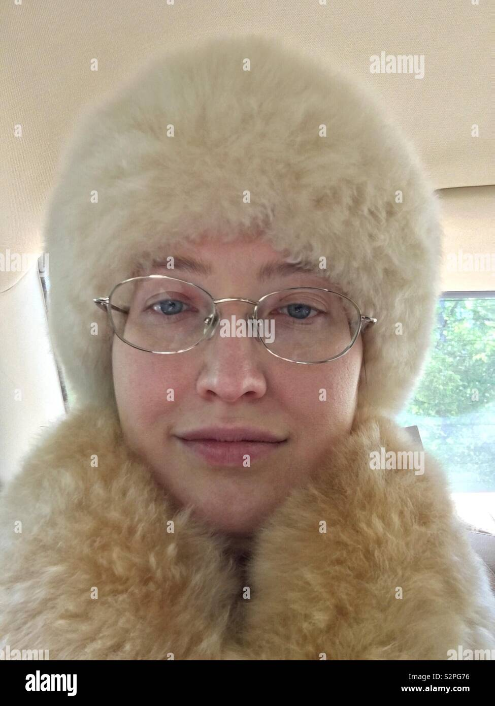 Caucasian woman with blue eyes and gold rimmed glasses inside car wearing cruelty free no-kill alpaca fur hat and scarf Stock Photo