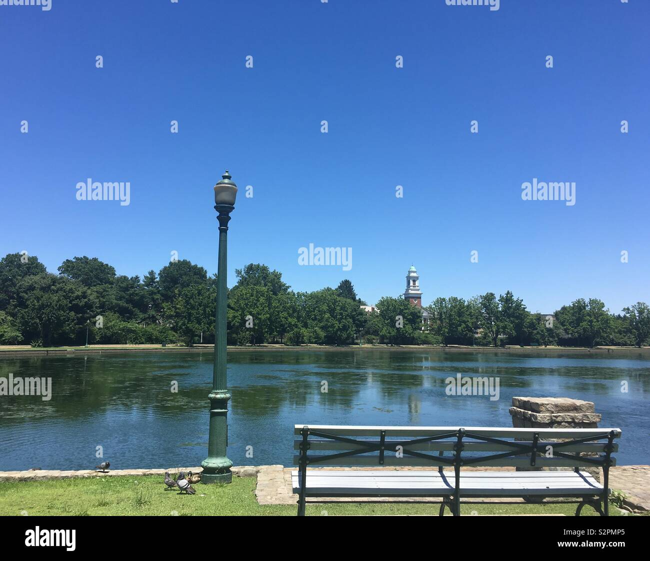 Park Bench by a lake - Stock Image