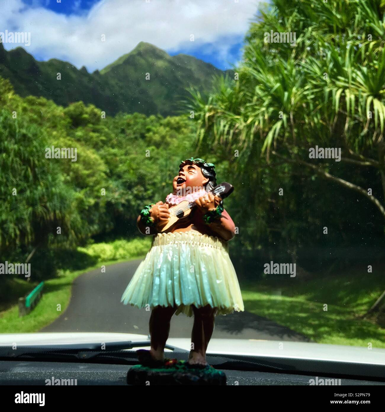 Hula bobblehead in a grass skirt on a car dashboard playing the ukulele while driving in Hawaii Stock Photo