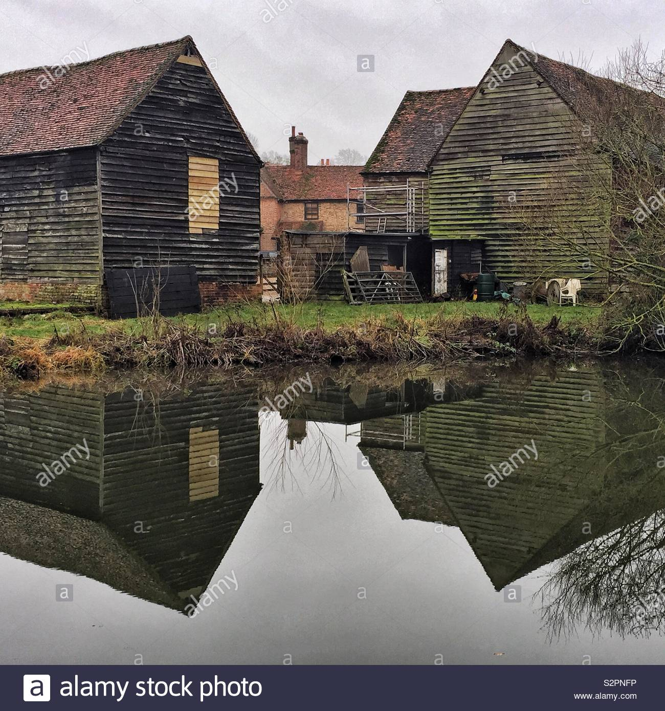 The reflection of two wooden barns in The Grand Union Canal near Rickmansworth - Stock Image