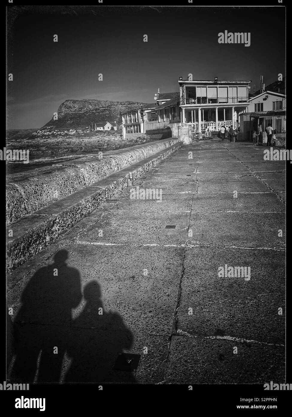 Shadows of two people walking along promenade at Kalk Bay Harbour, South Africa. - Stock Image