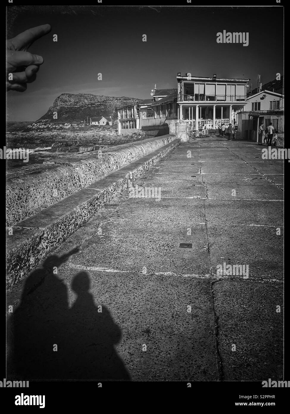 Shadow of people walking along promenade at Kalk Bay harbour, South Africa. - Stock Image