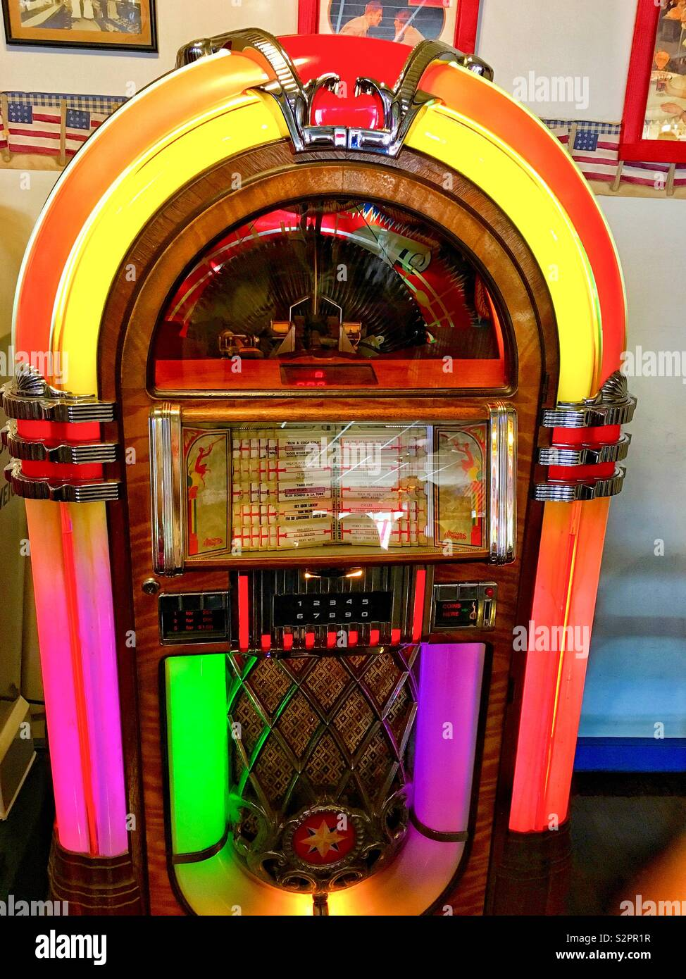 An old fashioned neon pink green orange and yellow nickelodeon aka jukebox sitting in old fashioned diner - Stock Image