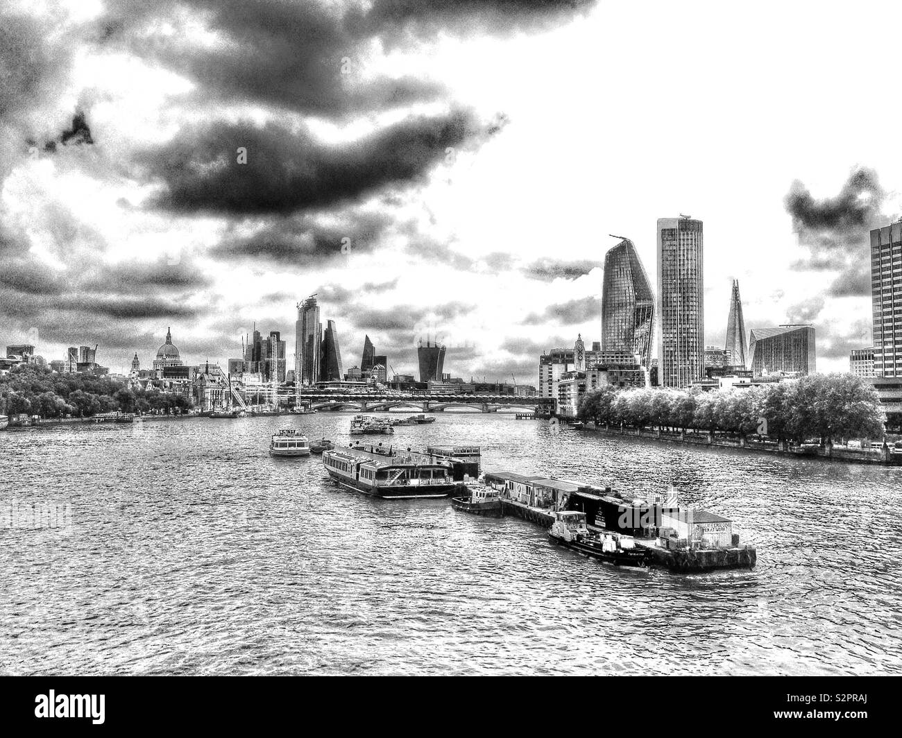 A view from Waterloo Bridge looking along the River Thames towards the City of London, England on an overcast day. - Stock Image