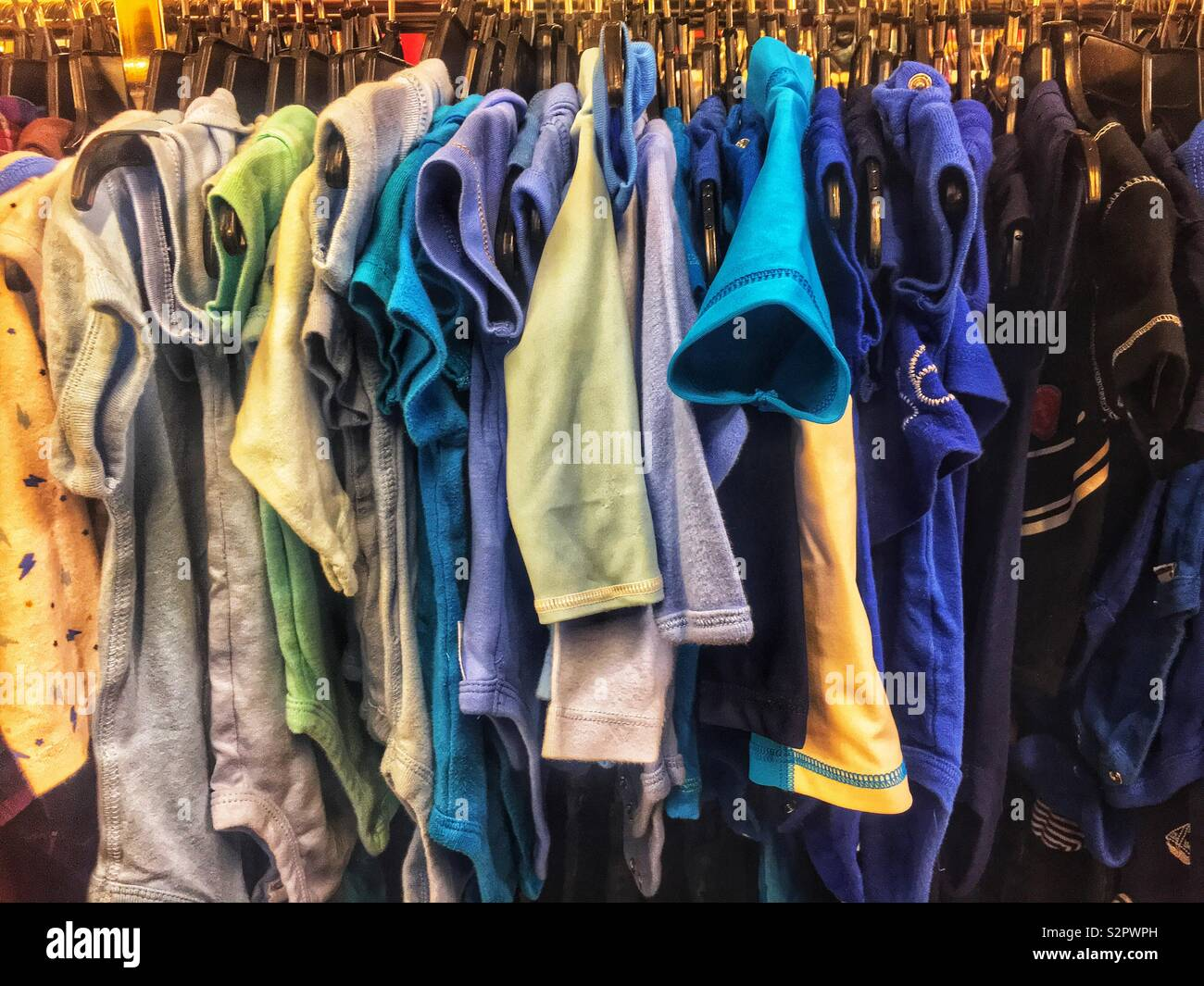 Many short sleeved cotton shirts of various bright colors and hanging on a rod. - Stock Image