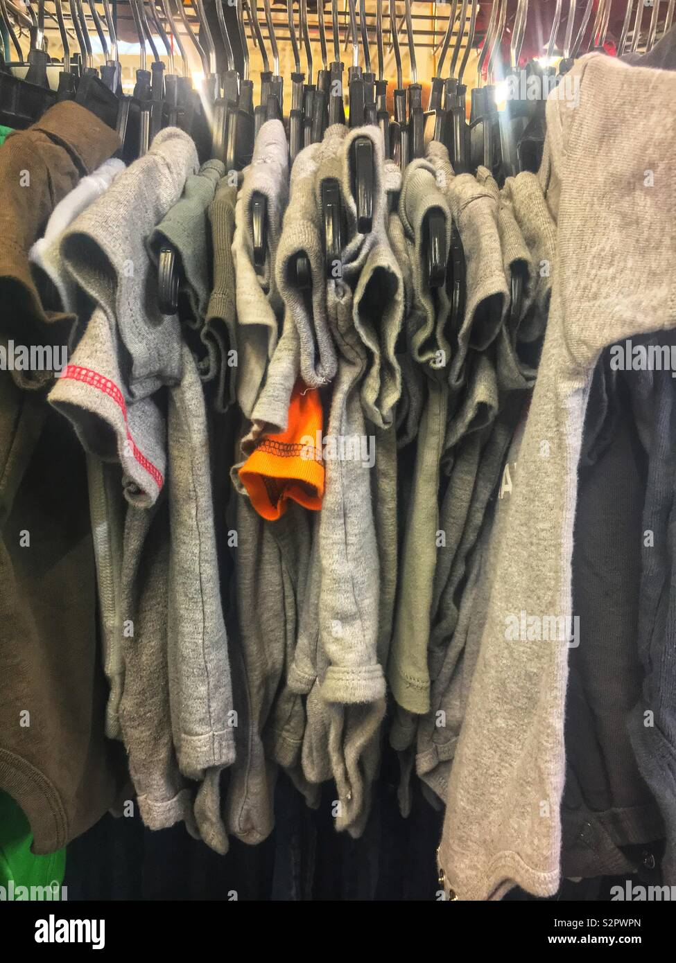 Many short sleeved cotton shirts of various grey colors and hanging on a rod. - Stock Image