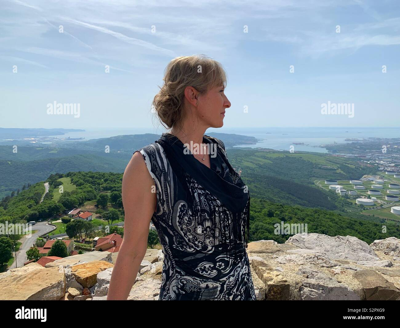 Woman looking at the horizon from the top of a castle wall. - Stock Image