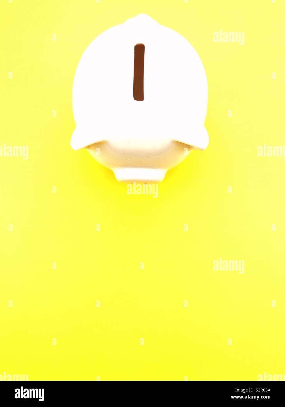 white coin bank on a yellow background - Stock Image