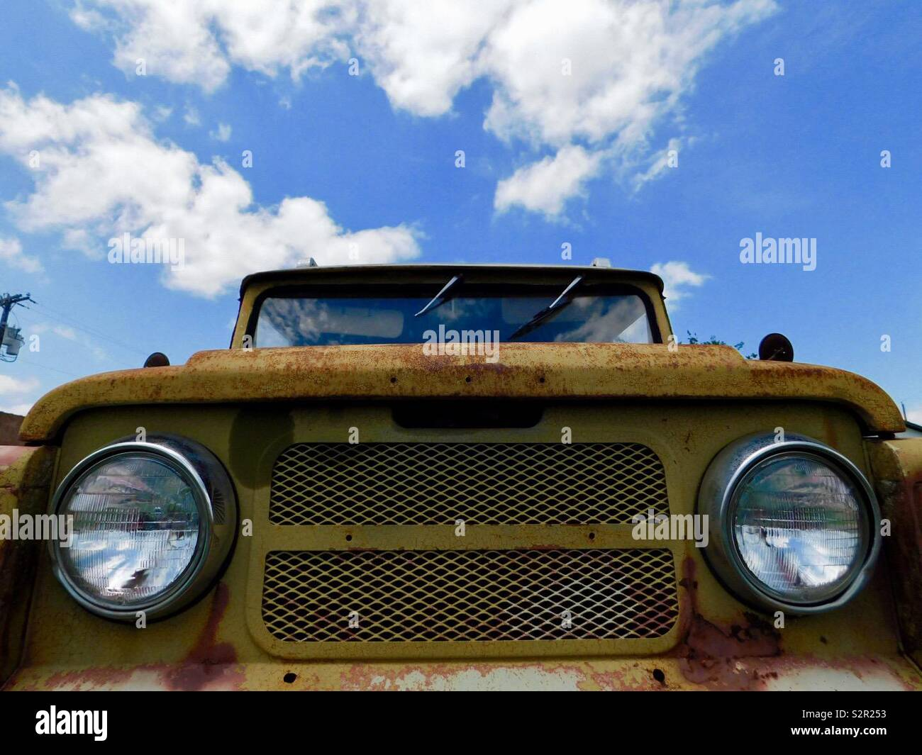 Yellow classic/vintage rusty front end of Jeep with headlights and grill agains a bright blue sky with fluffy clouds. - Stock Image