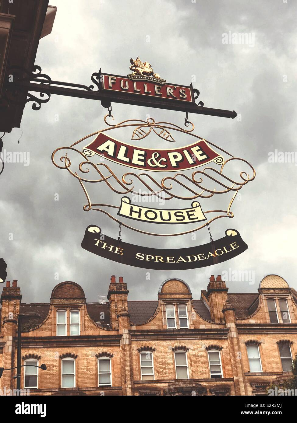 A traditional pub sign in London, England, silhouetted against a cloudy sky. - Stock Image