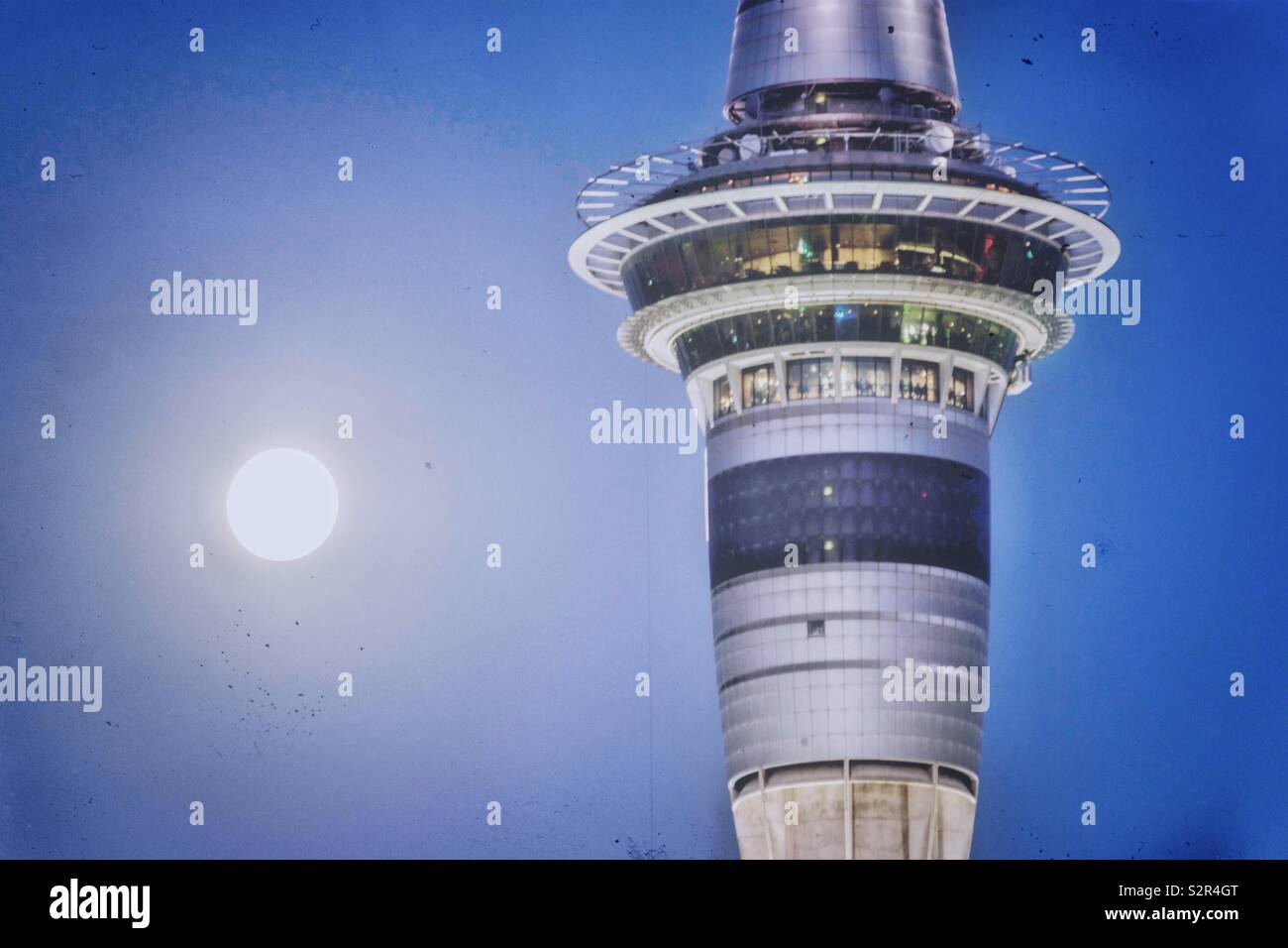 Moon rising beside the top of an entertainment tower in Auckland - Stock Image