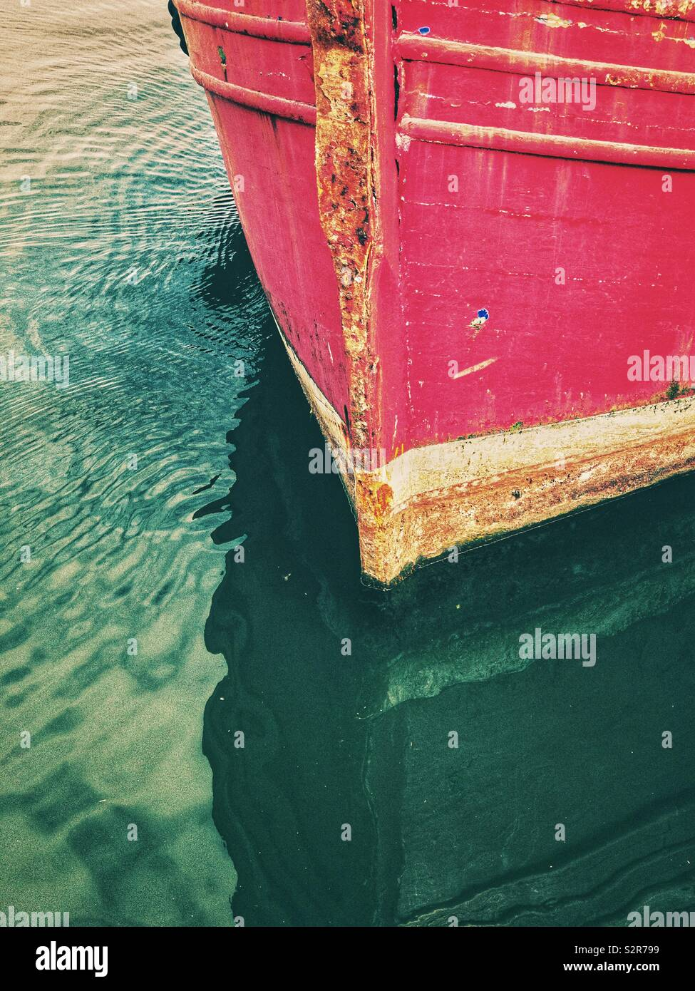 Now of old red boat with reflection in the water. - Stock Image