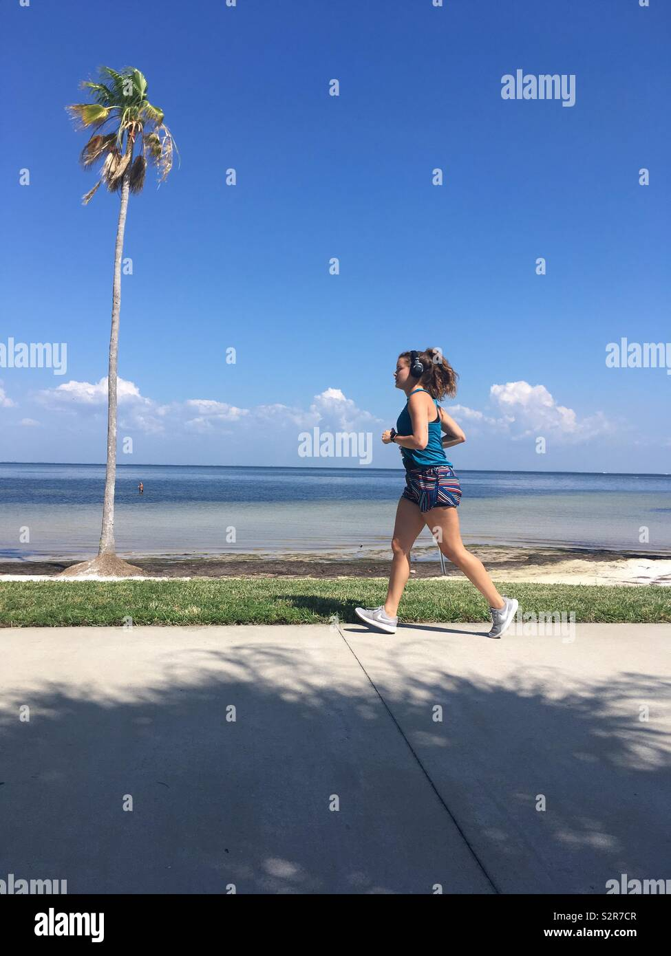 Woman running past palm tree - Stock Image