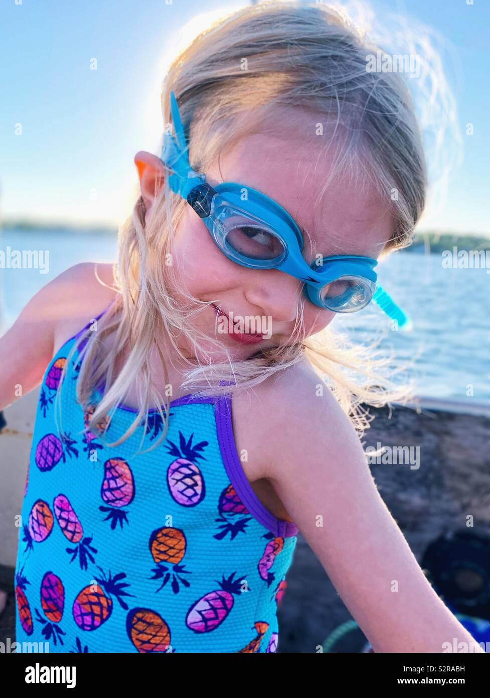 Young blonde girl wearing blue swim goggles and a swimsuit at the lake. Stock Photo