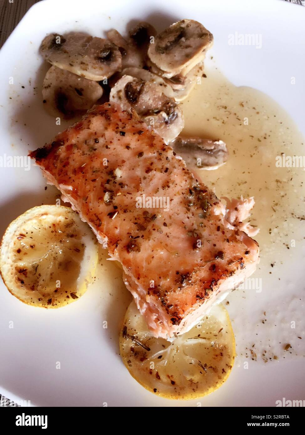 Gourmet entrée of broiled salmon fillet with lemon slices and fresh mushrooms, USA - Stock Image