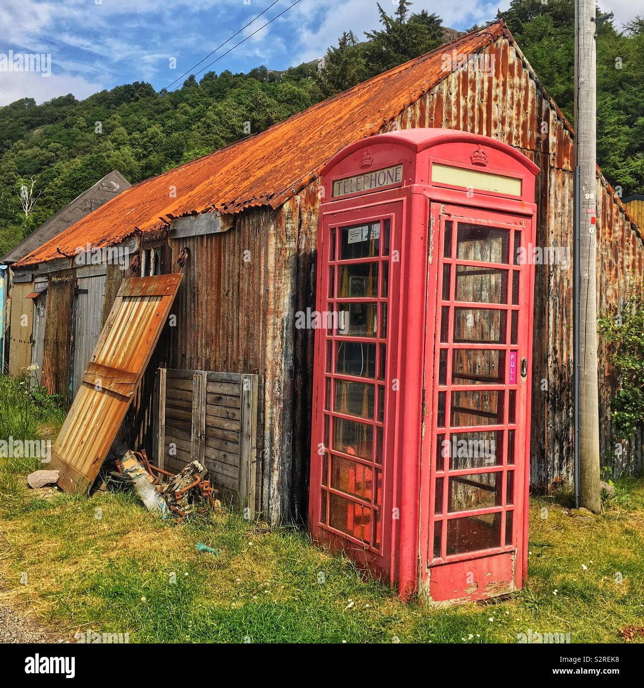 Red telephone box against dilapidated buildings. - Stock Image