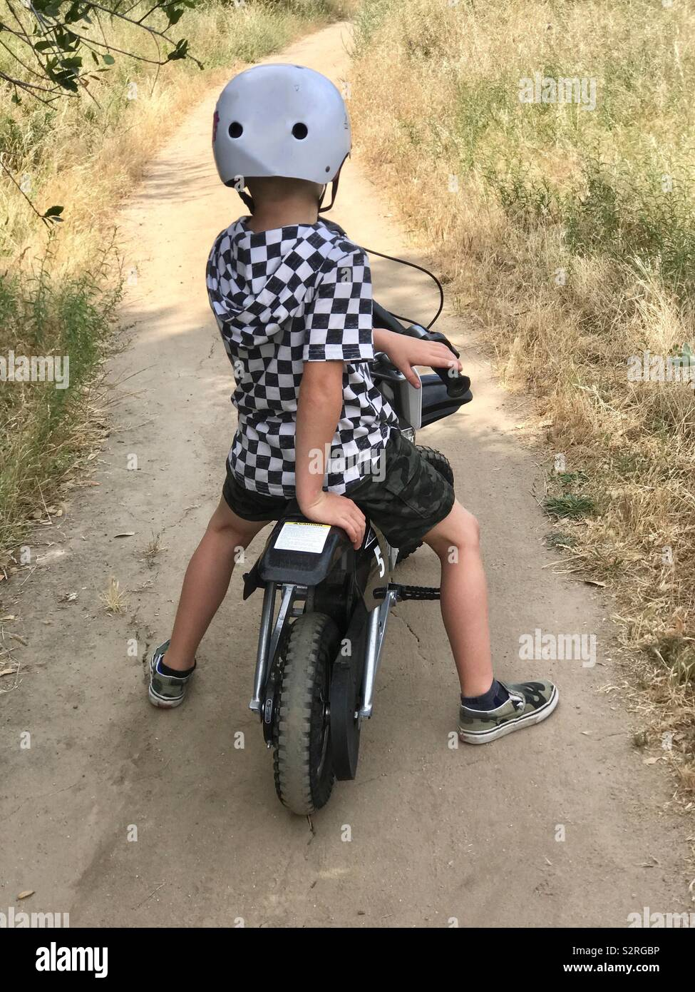 A young boy riding his dirt bike in the woods on a dirt pathway in the summer - Stock Image